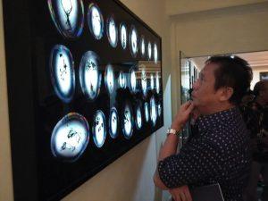Johnny Hendarta fotografer senior yang juga peserta pameran sedang mengamati karya pameran di Jogja Gallery
